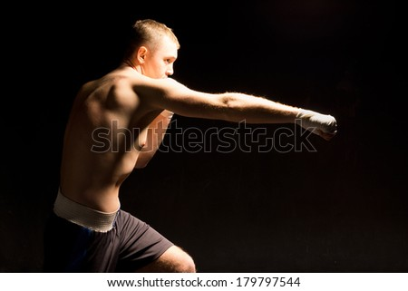 Boxer making a jabbing punch during a boxing match with his arm fully extended , dramatic lighting on a dark shadowy background - stock photo