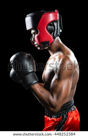 Boxer performing boxing stance on black background