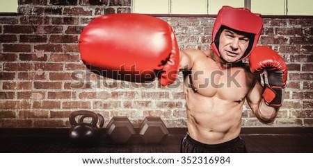 Boxer punching against black background against gym - stock photo