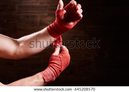Boxer putting bandage around wrists and hands against brown wall.