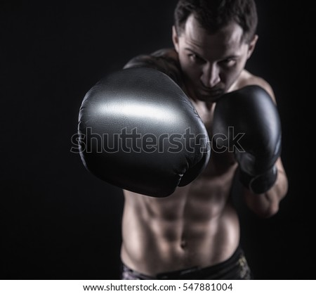 Boxer with boxing gloves before a fight on a black background. Boxing concept