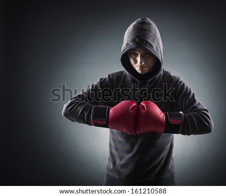 Boxer with red gloves in dark room - stock photo