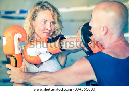 Boxer woman hitting with thai technique of elbow - Active lady with boxing gloves during martial arts training - Female athlete in fighting scene at mma center - Vintage filter and vignetting effect - stock photo