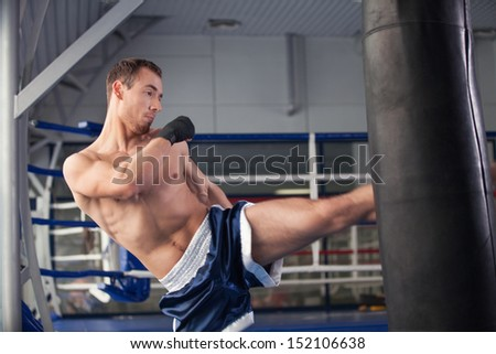 Boxer. Young kickboxer training at the punching bag - stock photo