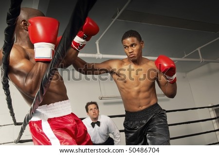 Boxers fighting in ring with referee watching - stock photo