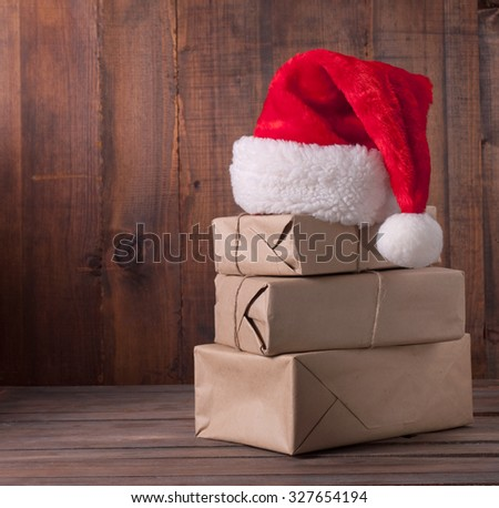 boxes with Christmas presents and santa hat on a wooden background