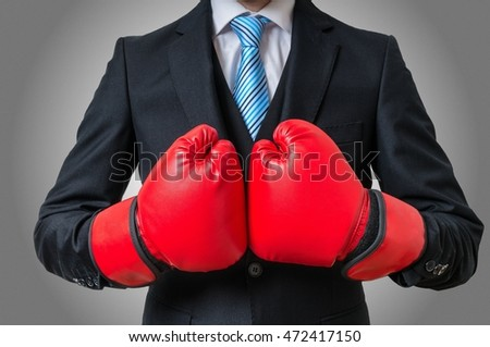 Boxing businessman with red gloves on gray background.