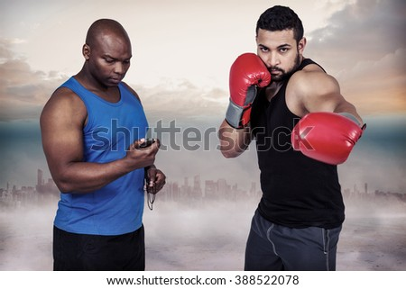Boxing coach with his fighter against cityscape on the horizon