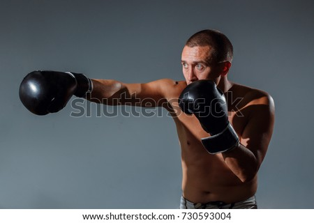 Boxing fighter trainning indoor on grey background