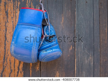 Boxing-glove hanging on wooden background. - stock photo