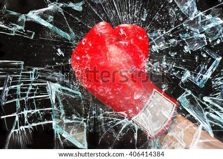 Boxing glove through broken glass window. - stock photo