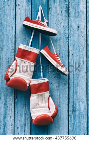 Boxing gloves and shoes hanging on a blue wooden wall - stock photo