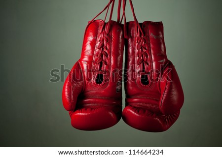 Boxing gloves hanging from laces on a grey background. - stock photo