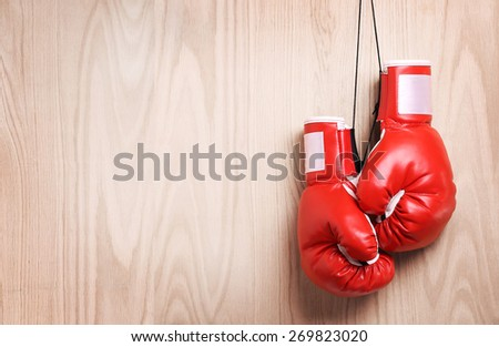 Boxing gloves over wooden background - stock photo
