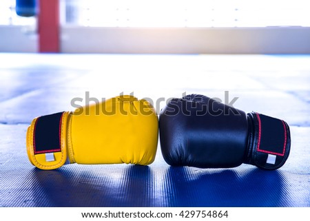Boxing Gloves Yellow VS Black on Blue rubber flooring - stock photo
