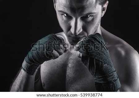 Boxing man ready to fight. Boxer with strong hands and clenched fists on a black background