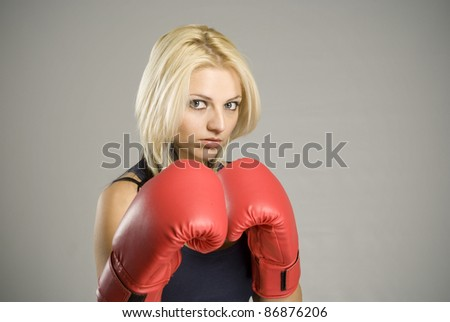 Boxing pose pretty fit blond woman boxer training or working out with red boxing gloves - stock photo