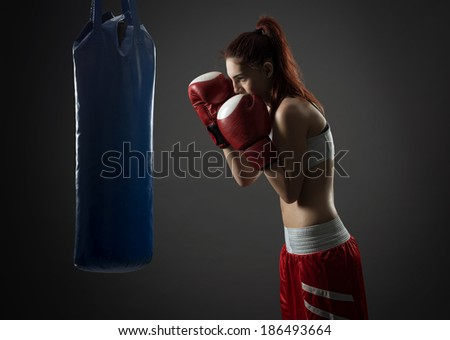 Boxing woman exercises with punching bag, on gray background