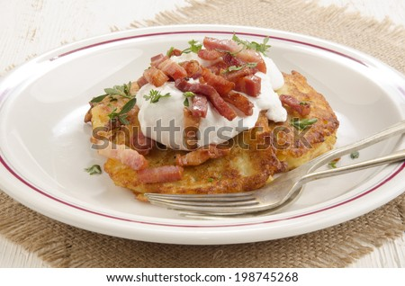 boxty, irish pancake with sour cream, bacon and parsley - stock photo