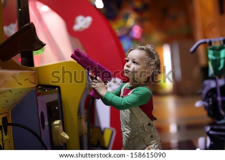 Boy aiming a gun at indoor playground - stock photo