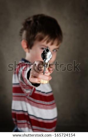Boy aiming toy gun, shallow focus - stock photo