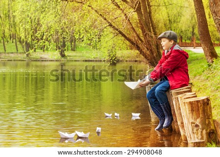 Boy alone near pond playing with  paper boats