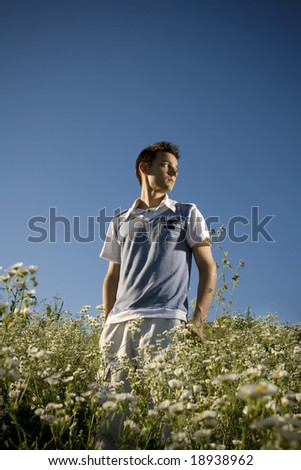 Boy among a field of daisies, with a clear blue sky as background and a peaceful atmosphere. - stock photo