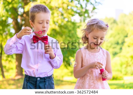 boy and a girl of 6 years on the meadow with bubbles - stock photo