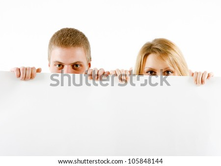 boy and a girl peeking from a white sheet of paper - stock photo