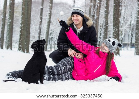 Boy and a girl playing with dog - stock photo