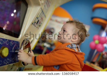 Boy and amusement car at indoor playground