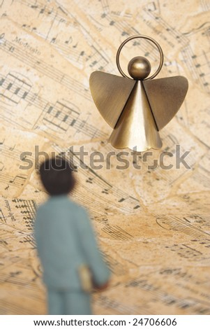 Boy and angel with a music sheet as back ground - stock photo