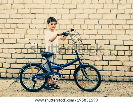 Boy and bicycle standing  against brick  wall toned image - stock photo