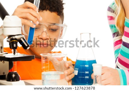 Boy and chemistry - 8 years old mixing liquids in test tubes and flasks - stock photo
