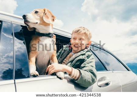 Boy and dog look out from car window - stock photo