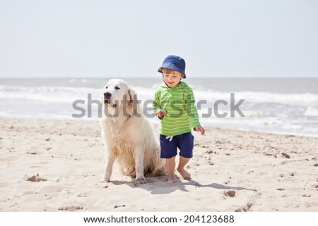 Boy and dog playing on beach  - stock photo