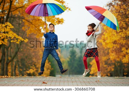 boy and girl among the leaves in autumn park - stock photo