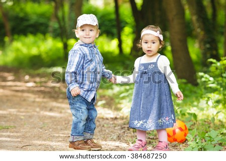 Boy and girl are playing with ball outdoor - stock photo