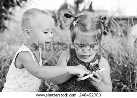 boy and girl are playing with phone outdoors - stock photo