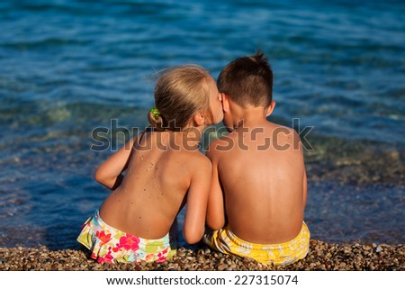 Boy and girl are sitting on the beach - stock photo