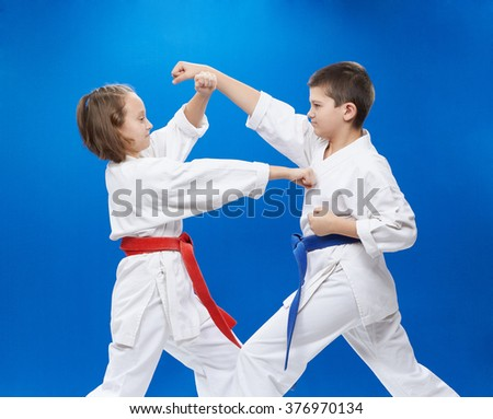 Boy and girl are trained karate punches and blocks - stock photo