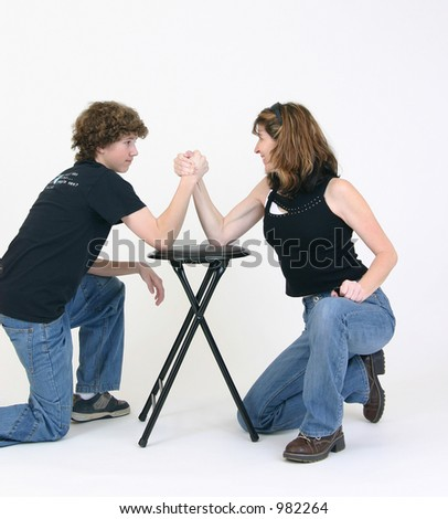 Boy and girl arm wrestling - stock photo