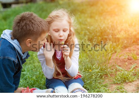 boy and girl blowing on dandelion - stock photo