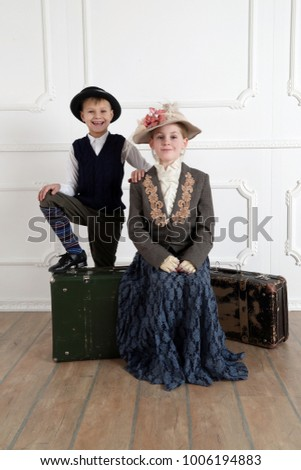 Boy and girl couple in vintage clothes and hats sit on old retro suitcases  waiting for travel