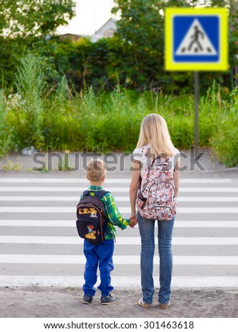 boy and girl crossing the road observing traffic rules - stock photo