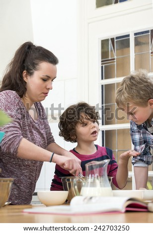 Boy and Girl discussing while mother mixing cupcake batter in kitchen - stock photo