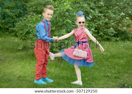 Boy and girl dressed in red and blue costumes dance at grassy lawn.