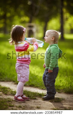 boy and girl drinking mineral water in park