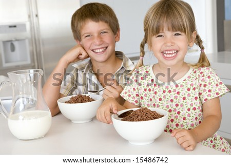Boy and Girl eating breakfast cereal at home
