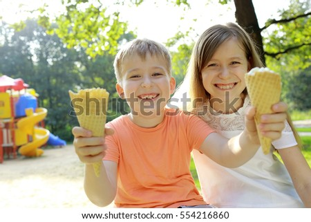 Boy and girl eating ice cream in park
